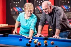 Reife Paare, die Pool spielen lizenzfreie stockfotos