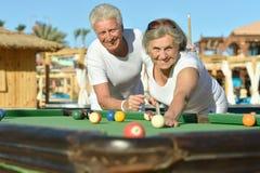 Reife Paare, die Pool spielen Stockfotografie