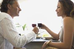 Reife Paare, die rösten und zu Mittag essen. Stockfotos