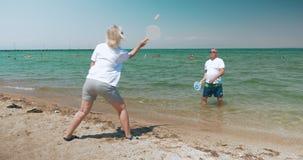 Reife Paare, die Schläger-Ball auf dem Strand spielen stock video