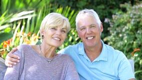 Reife Paare, die sich zusammen im Garten entspannen stock footage
