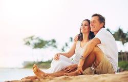 Reife Paare, die Sonnenuntergang auf dem Strand genießen Stockfotografie