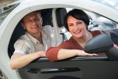 Reife Paare, die twizy elektrisches fahren stockfotografie