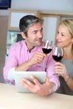 Reife Paare im trinkenden Wein der Küche Stockfotografie