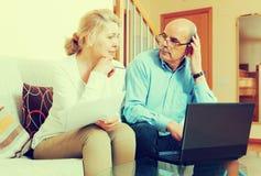 Reife Paare mit Dokumenten und Laptop Stockfotos