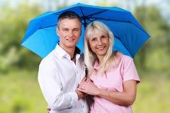 Reife Paare mit Regenschirm vor Naturhintergrund Stockbilder