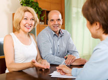 Reife Paare mit Versicherungsagenten Stockbild