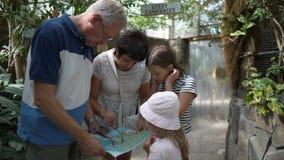 Reife Paare mit zwei Enkelinnen passen sorgfältig die Karte des Vergnügungsparks auf stock video footage