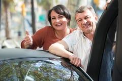Reife Paare nähern sich twizy elektrisches Lizenzfreie Stockfotos