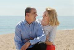Reife Paare am Sandstrand lizenzfreie stockfotos