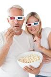 Reife Paare, welche die Gläser 3d essen Popcorn tragen Stockfoto