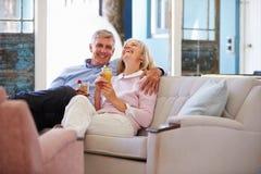 Reife Paare zu Hause, die im Aufenthaltsraum mit kalten Getränken sich entspannen lizenzfreie stockfotografie