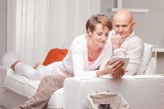 Reife Paarlesenachrichten in den digitalen Geräten Stockfoto