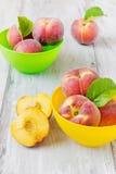Reife Pfirsiche in farbigen Schüsseln Stockbild