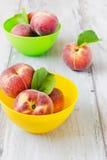 Reife Pfirsiche in farbigen Schüsseln Stockfotografie