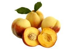 Reife Pfirsiche mit Blättern auf einem weißen Hintergrund. Lizenzfreie Stockfotos