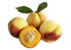 Reife Pfirsiche mit Blättern auf einem weißen Hintergrund. Stockfotos