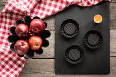 Reife rote Äpfel auf hölzernem Brett mit rotem kariertem Tuch um und Zubehör für das Backen lizenzfreie stockbilder