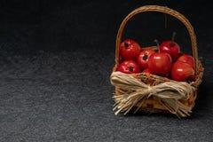 Reife rote Äpfel, die in einem Strohkorb sitzen Kopieren Sie Raum auf einem Schwarzen lizenzfreies stockbild