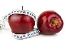 Reife rote Äpfel und ein Maßband Lizenzfreies Stockbild