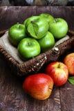 Reife rote Äpfel und grüner Apfel auf hölzernem Hintergrund Stockfoto