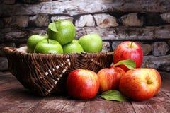 Reife rote Äpfel und grüner Apfel auf hölzernem Hintergrund Stockfotografie