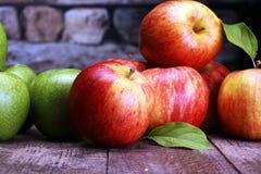 Reife rote Äpfel und grüner Apfel auf hölzernem Hintergrund Stockbilder