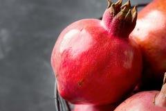 Reife rote Granatäpfel im Weinlese-Metallkorb auf dunklem Steinhintergrund-Fall Autumn Thanksgiving Lizenzfreies Stockfoto