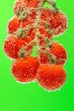Reife rote Kirschtomaten auf der Niederlassung versenkt in Wasser mit Blasen lizenzfreies stockfoto