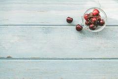 Reife rote süße Kirschen auf blauem hölzernem Hintergrund Flache Lage Bunte Di?t und gesundes Lebensmittelkonzept stockfoto