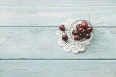Reife rote süße Kirschen auf blauem hölzernem Hintergrund flache Lageart Bunte Di?t und gesundes Lebensmittelkonzept lizenzfreies stockfoto