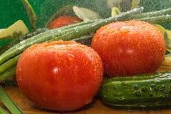 Reife rote Tomaten, grüne Gurken, Frühlingszwiebelfedern werden mit großen Wassertropfen bedeckt Stockfotografie