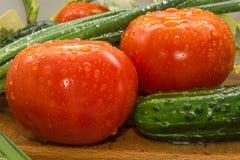 Reife rote Tomaten, grüne Gurken, Frühlingszwiebelfedern werden mit großen Wassertropfen, Zusammensetzung auf einem hölzernen bed Stockbilder