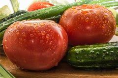 Reife rote Tomaten, grüne Gurken, Frühlingszwiebelfedern werden mit großen Wassertropfen, Zusammensetzung auf einem hölzernen bed Lizenzfreies Stockbild