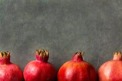 Reife rote vibrierende organische Granatäpfel vereinbart in der Grenze auf schwarzem Steinhintergrund-Plakat-Gruß-Karten-Schablon Stockfoto