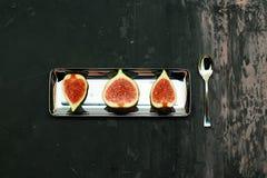 Reife süße Feigen, Frucht mit Hälfte und Viertel auf dunklem Hintergrund Stockfotos