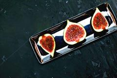 Reife süße Feigen, Frucht mit Hälfte und Viertel auf dunklem Hintergrund Lizenzfreie Stockfotos