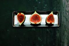 Reife süße Feigen, Frucht mit Hälfte und Viertel auf dunklem Hintergrund Stockfotografie