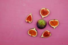 Reife süße Feigen, Frucht mit Hälfte und Viertel auf rosa Hintergrund Stockbild