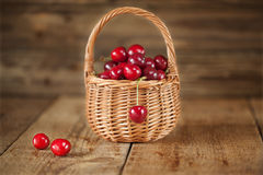 Reife süße Kirschen im Korb auf rustikalem hölzernem Hintergrund Stockbild