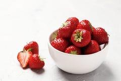 Reife saftige Erdbeeren in einer Schüssel auf einem hellen Hintergrund stockfotografie