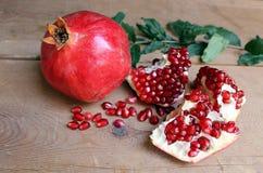Reife saftige Früchte des Granatapfels auf dem Holztisch Stockfotografie