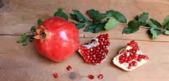 Reife saftige Früchte des Granatapfels auf dem Holztisch Stockfotos