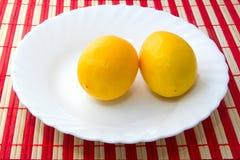 Reife saftige Zitronen auf Platte Stockbild