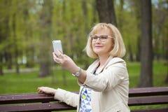 Reife Schönheit liest die Mitteilung am Telefon Lizenzfreie Stockfotografie