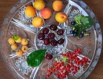Reife schwarze Johannisbeeren, Kirschen, rote Johannisbeeren, Aprikosen auf Crystal Plate Beschneidungspfad eingeschlossen Lizenzfreies Stockfoto