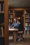 Reife Studenten, die in der Collegebibliothek zusammenarbeiten Lizenzfreie Stockfotos