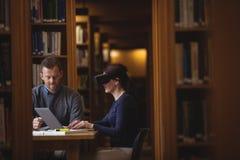 Reife Studenten, die in der Collegebibliothek zusammenarbeiten Lizenzfreie Stockbilder