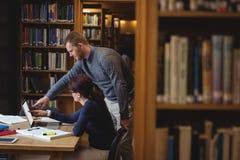 Reife Studenten, die in der Collegebibliothek zusammenarbeiten Stockbilder