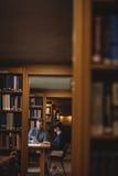 Reife Studenten, die in der Collegebibliothek zusammenarbeiten Stockbild